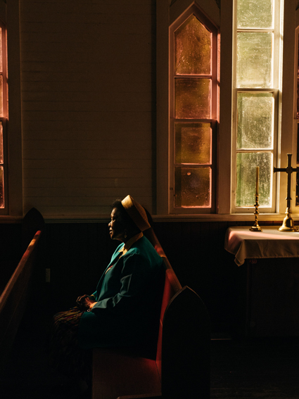 A woman sits in a church pew in Blackwater Heights by Robbie Lawrence