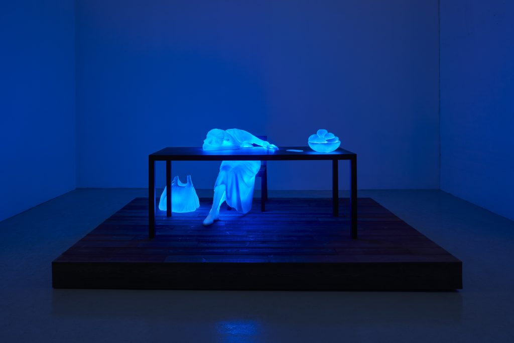 A woman slumped over a table appears lit from the inside in this image by Doug Aitken