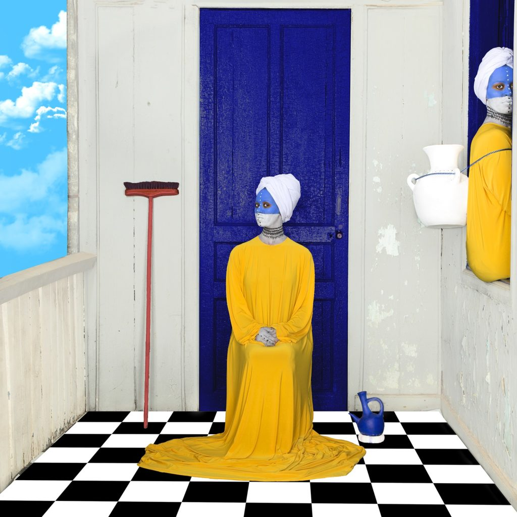 Woman in yellow dresses with their faces painted blue and white sit in front of blue doors. Part of our round-up of must-see photography in October 2019.