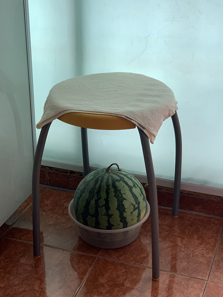 A watermelon sits in a bowl underneath a stool covered with a towel.